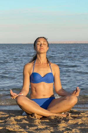 Young woman rests on the beach on a hot summer day. Young attractive smiling woman practicing yoga on a sea. Healthy active lifestyle concept. vertical photo.