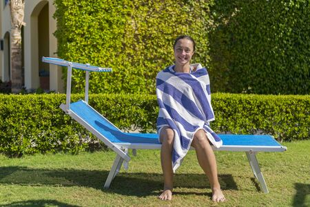 Woman wipes off a towel sitting on sunbed.