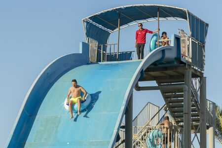 Hurghada, Egypt. November 19 2018 The guy with the girl down the water slide. The girl is afraid to go down the hill. Couple at the water park