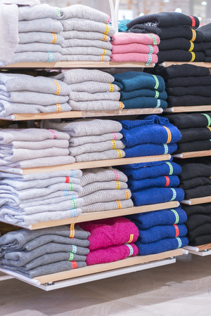 Neatly folded clothes. Rack of clothes with warm. Wooden cabinet with a stack of sweaters. Coloured clothing. Neat stacks of folded clothing on the shop shelves. vertical photo. 免版税图像