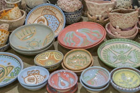 Variety of Colorfully Painted Ceramic Pots in an Outdoor Shopping Market. pottery in the shop window 免版税图像