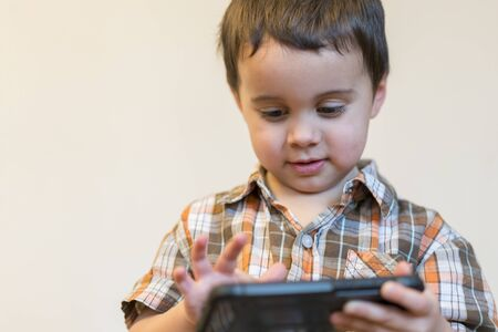 Portrait of a smiling little boy holding mobile phone isolated over light background. cute kid playing games on smartphone.
