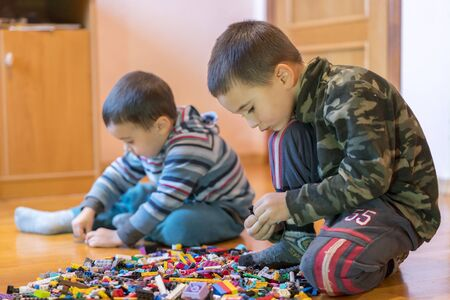 Two children playing with lots of colorful plastic blocks constructor sitting on a floor indoor. Two little brothers play constructor. Communication and friendship.