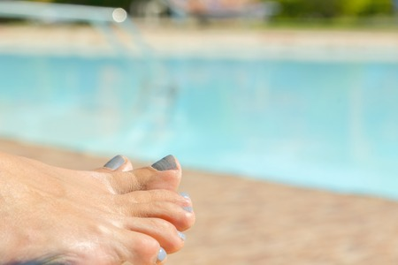 girls legs by pool. Relaxing at the pool. womans feet against swimming pool on resting.