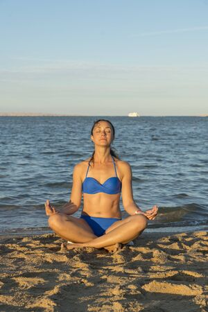 Young woman rests on the beach on a hot summer day. Young attractive smiling woman practicing yoga on a sea. Healthy active lifestyle concept. Reklamní fotografie