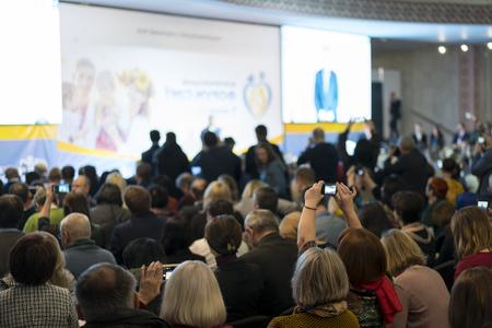 Leute im Konferenzsaal. Rückansicht. Die Leute im Saal hören dem Dozenten zu.