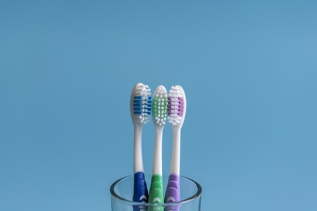 Set of toothbrushes in glass on blue background. Cup with toothbrushes against color background. Dental care. Фото со стока