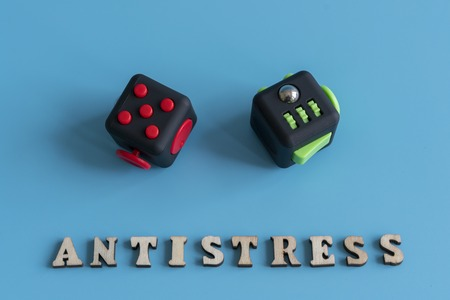 Fidget Cube stress reliever, Fingers Toy on a blue background. Inscription antistress. Stock Photo