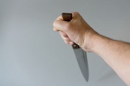 Mans hand with a knife on gray background. Concept of violence. Hand of a gangster with a knife. copy space