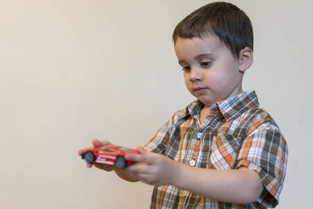Toddler boy with a red toy car. copy space.