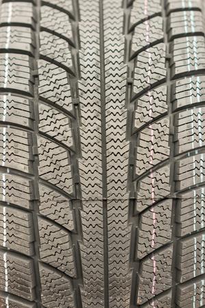 Close-up winter tire tread. Textured tire tread. Part of brand new modern winter car tire. vertical photo.