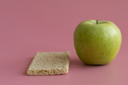 crunchy loaves of bread and Apple on a pink background. Concept of losing weight and healthy lifestyle. Stock fotó