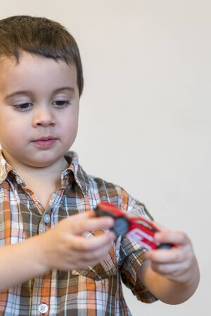 Toddler boy with a red toy car. copy space. vertical photo. Stok Fotoğraf