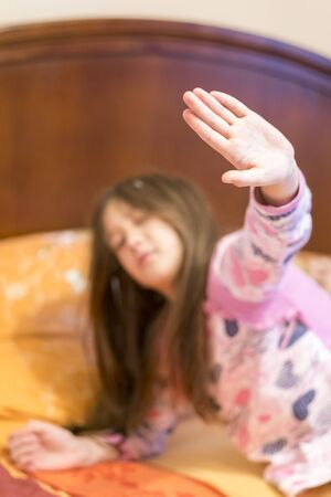 Cute little girl stretching her arms happily with a smile from waking up in her bed. child sleepy yawning in bed. Sleepy little girl on the bed. vertical photo.