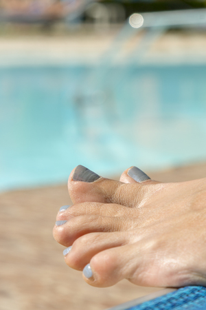 girls legs by pool. Relaxing at the pool. womans feet against swimming pool on resting. vertical photo.