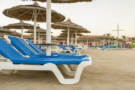 Umbrellas and chaise lounges on the beach. Scenic view of private sandy beach with sun beds from the sea.