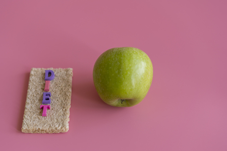 crunchy loaves of bread and Apple the inscription diet on a pink background. Concept of losing weight and healthy lifestyle.