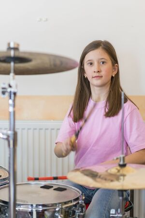 Little caucasian girl drummer playing the elettronic drum kit and shuoting. Teen girls are having fun playing drum sets in music class. Close-up photo. vertical photo. Stok Fotoğraf