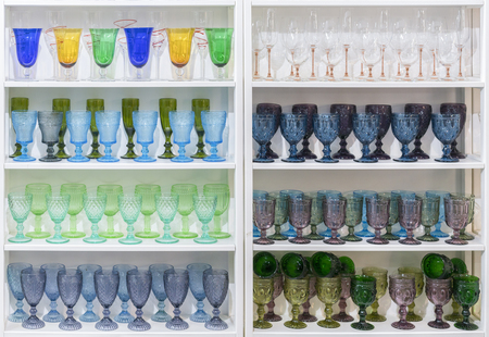 Colorful glasses and vases on the shelf in the souvenir shop. wine glasses stand on the shelves in a large supermarket.