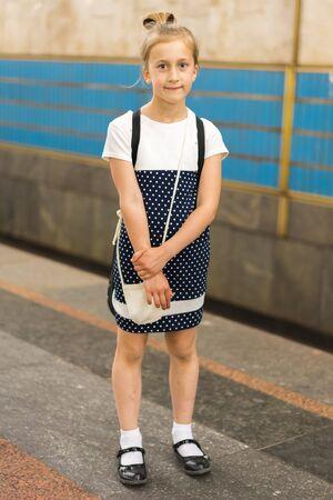 Little schoolgirl on the platform in the subway. vertical photo 写真素材