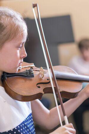 Bambino, bambina che suona il violino in casa in classe di musica. foto verticale.