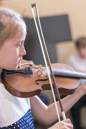 Child, little girl playing violin indoors in music class. vertical photo.