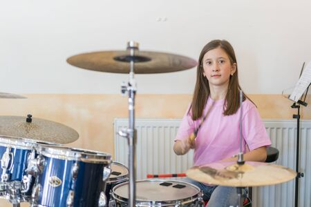 Little caucasian girl drummer playing the elettronic drum kit and shuoting. Teen girls are having fun playing drum sets in music class. Close-up photo