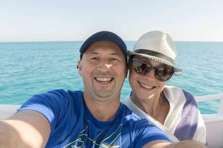 Happy middle aged couple taking selfie on yacht. Beautiful happy couple taking selfie on yacht deck floating in sea. Sailing, technology, tourism, travel and people concept,making vlog, vlog concept.
