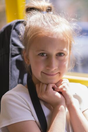 A little girl is going by bus. Schoolgirl sitting in school bus and ready for her first ride. vertical photo.