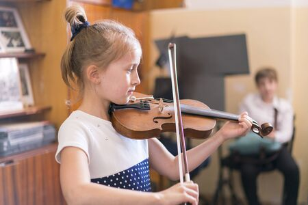 Child, little girl playing violin indoors in music class.