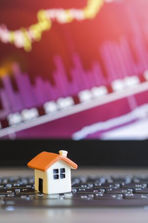 Growing home sale grap. model of the house on the background of growth graph. vertical photo. Stock Photo