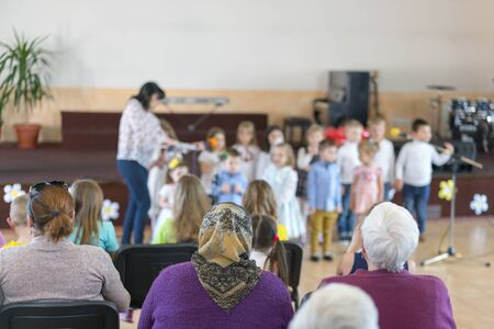 Performance by talented children. Children on stage perform in front of parents. image of blur kid s show on stage at school , for background usage. Blurry. 스톡 콘텐츠
