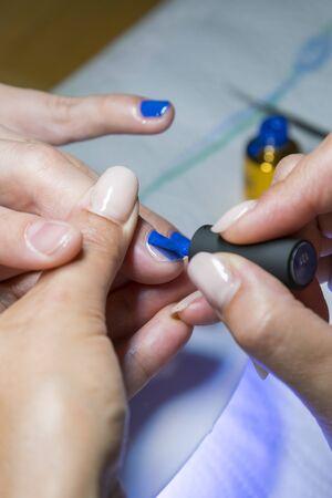 Schöner Maniküreprozess. Nagellack wird auf die Hand aufgetragen und hat eine blaue Farbe. Nahaufnahme. vertikales Foto. Standard-Bild
