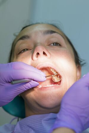 Dentist and patient in dentist office. Close-up of dental drill use for patient teeth in dentistry office in a dental treatment procedure. Woman having teeth examined at dentists. ertical photo.