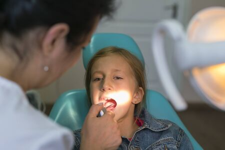 Close up portrait of a little smiling girl at dentist office. Girl at the dentist. Dentist examining little girls teeth in clinic. people, medicine, stomatology and health care concept.