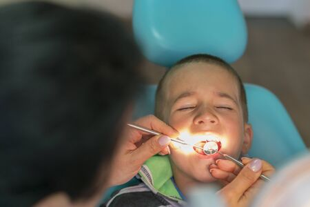 Pediatric dentist examining a little boys teeth in the dentists chair at the dental clinic. A child with a dentist in a dental office. Close up of boy having his teeth examined by a dentist.