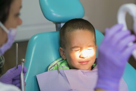 Pediatric dentist examining a little boys teeth in the dentists chair at the dental clinic. A child with a dentist in a dental office. Close up of dentist examination little boys teeth in clinic.