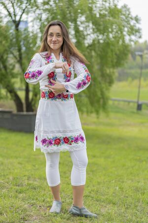 Happy young woman in the Ukrainian national clothes in the park. Woman in embroidery. Vertical photo.