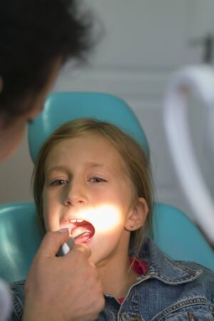 Close up portrait of a little smiling girl at dentist office. Dentist examining little girls teeth in clinic. people, medicine, stomatology and health care concept. vertical photo. Stock Photo