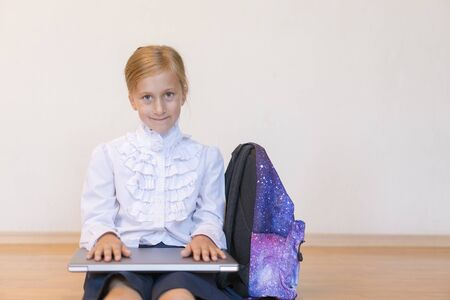 Schoolgirl with a laptop. the girl does exercises at a laptop. Back to school. copy space.