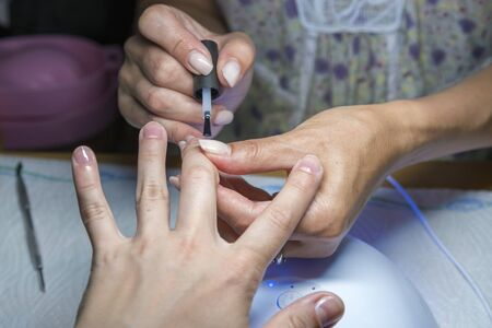 Beautiful manicure process. Nail polish being applied to hand, polish is a blue color. close up.