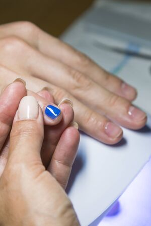 Beautiful manicure process. Nail polish being applied to hand, polish is a blue color. close up. vertical photo.