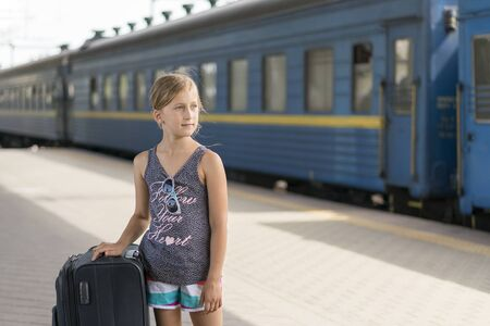 little sweet girl with a big suitcase on a deserted railway platform. girl pulling a large suitcase on the platform.