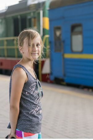 Little girl at the train station on the background of the train. Adventure and Travel Concept. vertical photo.