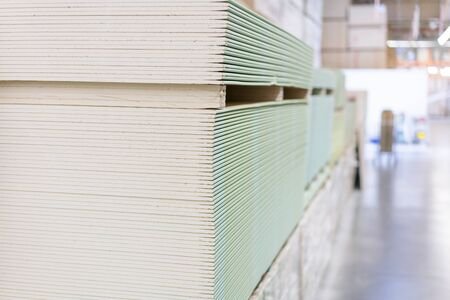 Gypsum plasterboard in the pack. The stack of gypsum board preparing for construction. Pallet with plasterboard in the building store. Construction Materials. Drywall warehouse.