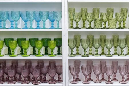 Colorful glasses and vases on the shelf in the souvenir shop. wine glasses stand on the shelves in a large supermarket