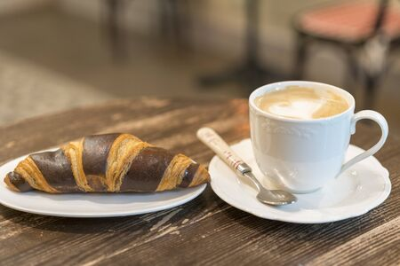 Fresh and tasty croissants with chocolate and cup of coffee on wooden background.