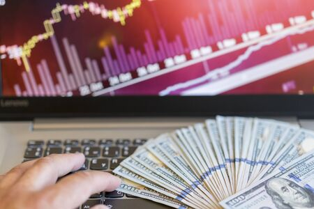 Dollar bills laying on a laptop with bitcoin charts on a blurred background.