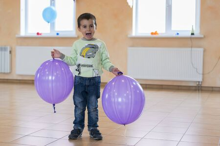 Little boy with big balloons. Happy kid with purple balloons in the hall
