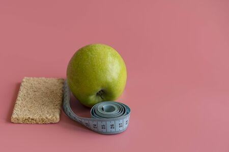 Dieting Concept Green Apple and waist line on a pink background. copy space. Banco de Imagens